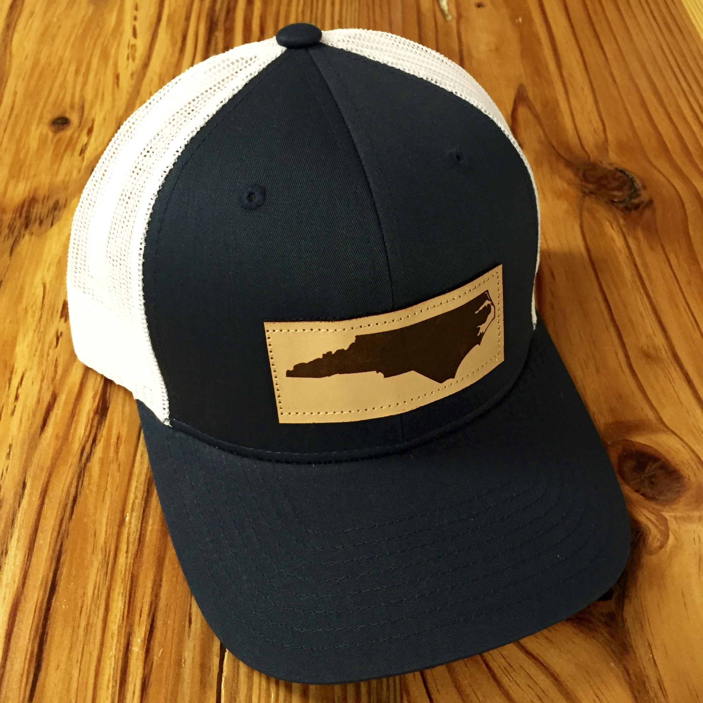 2c5f87b0ea5 Captuer Mesh Back North Carolina Leather Patch Trucker Hat Navy White  Accessories